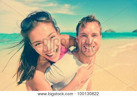 Portrait of happy young man giving piggyback ride to woman at beach. Excited couple are enjoying their summer vacation. Multiethnic tourists are having fun on shore.