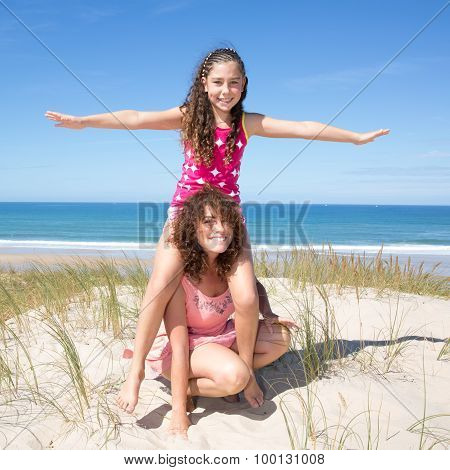 Young Girl Sits Astride On The Shoulders Of Her Mother
