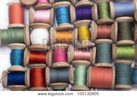 colored cotton thread for sewing on wooden spools on a white background
