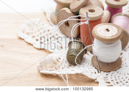 cotton thread for sewing, wound on a wooden spool, white lace and a metal thimble, vintage, on woode