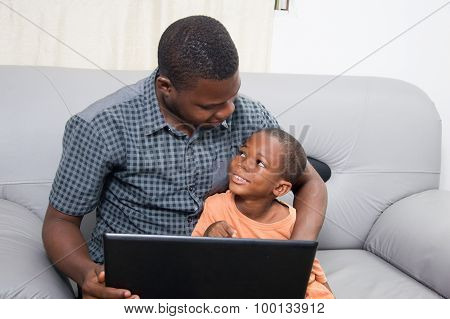 Father and child with a laptop.