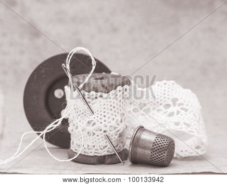 old wooden coil wound with hand-made lace and sewing accessories, needle, thimble and shabby old bla