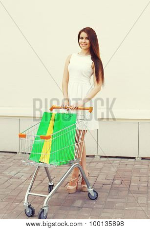 Beautiful Young Smiling Woman In White Dress And Cart With Shopping Colorful Bags