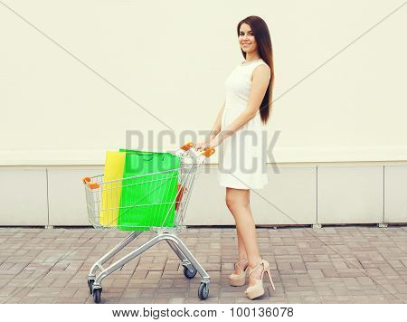Happy Beautiful Young Smiling Woman In White Dress And Cart With Shopping Colorful Bags