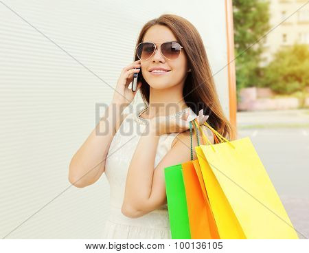 Portrait Of Happy Beautiful Young Smiling Woman With Shopping Colorful Bags Using And Talk On The Sm