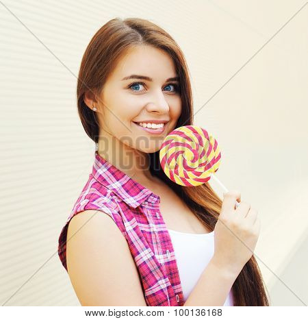 Portrait Of Pretty Young Girl Wearing A Pink Clothes With Sweet Caramel Having Fun Outdoors