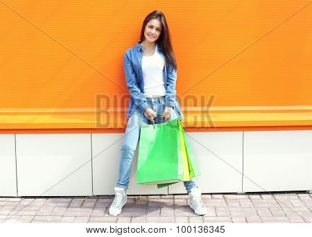 Beautiful Girl With Shopping Bags In Jeans Clothes Over Orange Wall