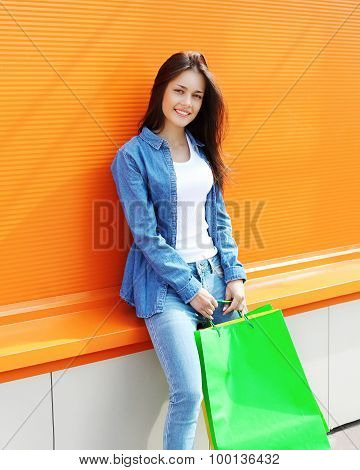 Portrait Of Beautiful Young Woman With Shopping Bags Over Colorful Orange Wall