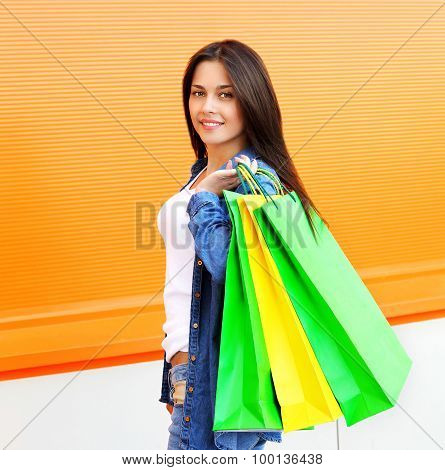 Portrait Of Beautiful Young Woman With Shopping Bags Over Orange Wall