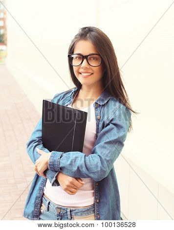 Portrait Of Smiling Student Girl In Glasses With Folder Outdoors