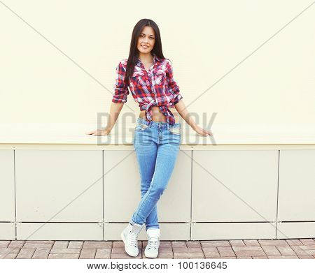 Pretty Young Woman Wearing A Checkered Shirt And Jeans Posing In The City Over White Wall