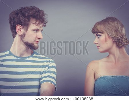 Woman And Man Sitting On Sofa Looking To Each Other.