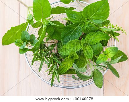 Fresh Green Herbs Harvest From Garden In The Basket On Wooden  Background .
