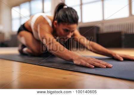 Female Performing Yoga On Exercise Mat At Gym