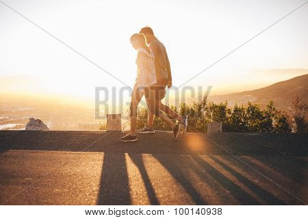 Couple Walk Along Road At Sunrise
