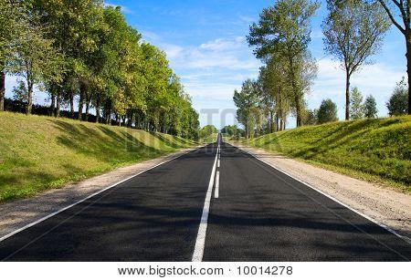 Black Serpentine Of Asphalt Road In Sunny Day.