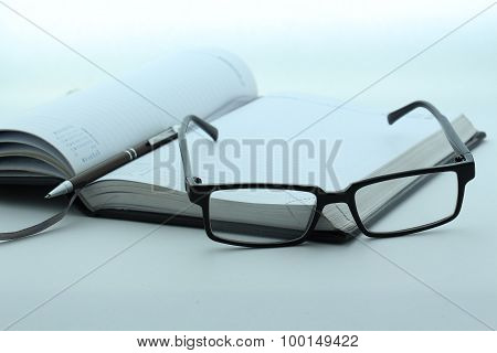 Diary, pen and glasses