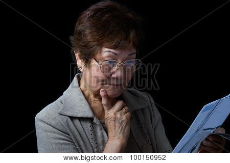 Senior Woman Surprised By Her Financial Bills On Black Background
