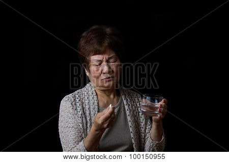 Senior Woman Taking Her Pills With Water
