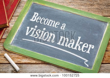 Become a vision maker - motivational advice on a slate blackboard with a white chalk and a stack of books against rustic wooden table