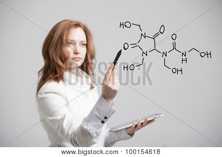 Woman chemist shows a molecular structure, on grey background