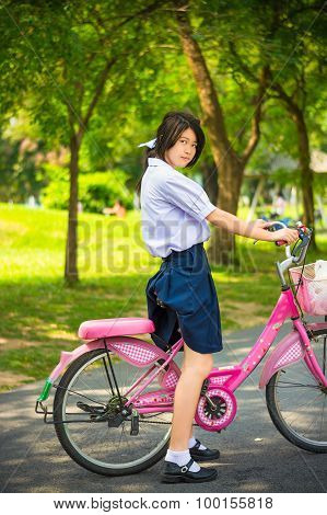 Cute Asian Thai schoolgirl student in high school uniform fashion is standing over her pink bicycle