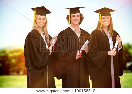 Three smiling students in graduate robe holding a diploma against sun rise over trees