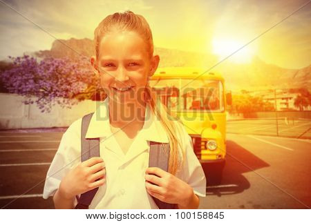 Cute pupil smiling at camera by the school bus against yellow school bus waiting for pupils