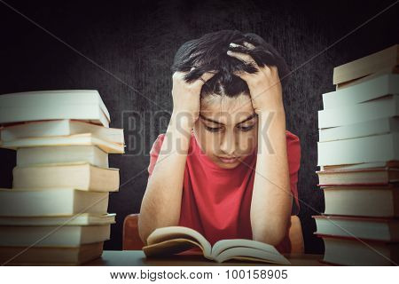Tensed boy sitting with stack of books against black
