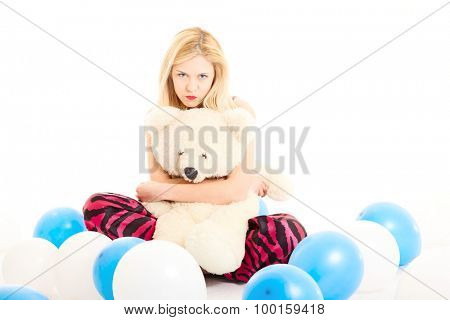 attractive girl in pajamas with teddy bear and balloons. portrait