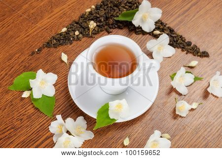 white cup and saucer with jasmine flowers on a wooden table. view from above