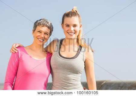 Portrait of sporty mother and daughter smiling at promenade