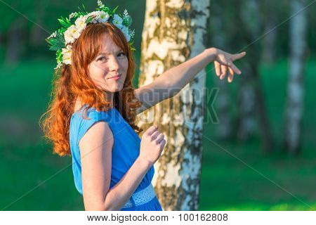 Girl With Red Hair In A Blue Dress Shows The Way