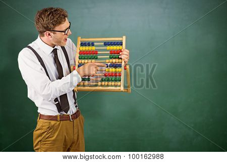 Geeky businessman using an abacus against green chalkboard