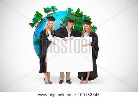 Three students in graduate robe holding and pointing a blank sign against white background with vignette