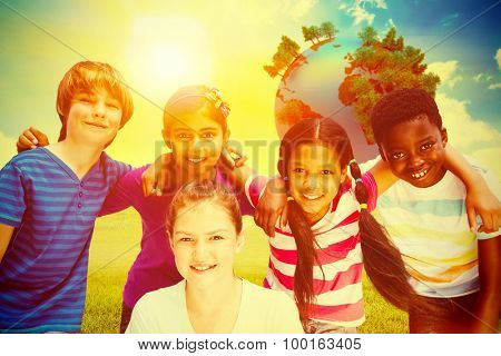 Happy children forming huddle at park against blue sky over green field