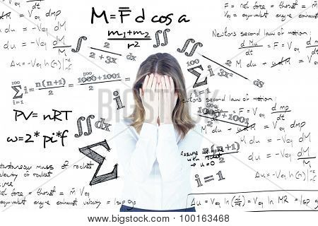 Anxious businesswoman with head in hands against maths equation