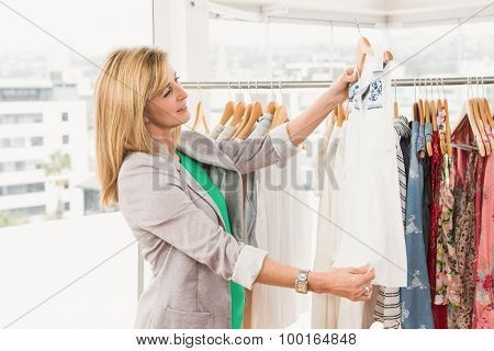 Smiling woman browsing clothes in clothing store