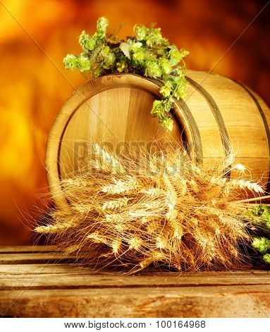 Wooden barrel with green hops and ears of wheat on table. Beer brewing concept. Brewing traditions. Vertical photo