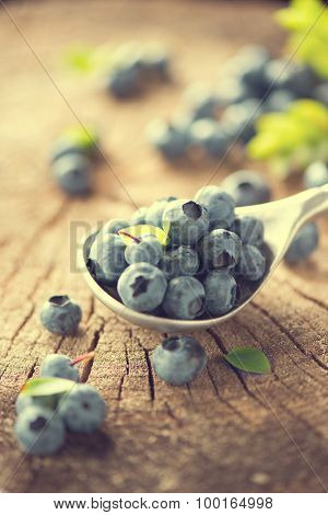 Blueberry in spoon on wooden table background. Ripe and juicy fresh picked bilberries closeup on Weathered Wood Boards for a Vintage Look. Blueberries close up. Vertical photo