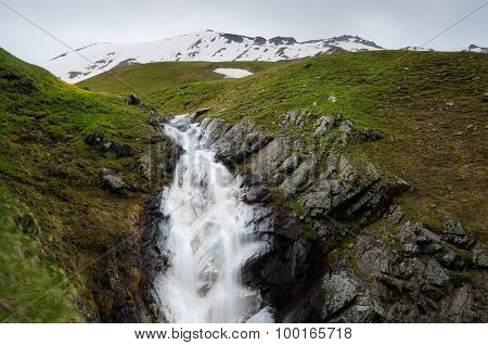Cloudy day in the mountains. Waterfall on the mountain river with chalk in water. Main Caucasian ridge. Zemo Svaneti, Georgia