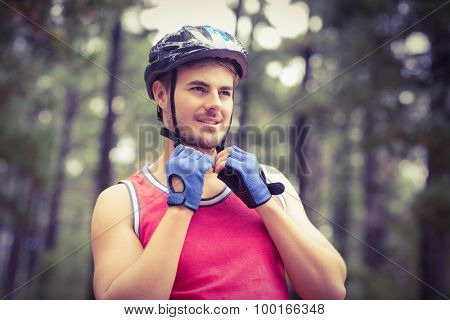 Handsome young biker looking away in the nature