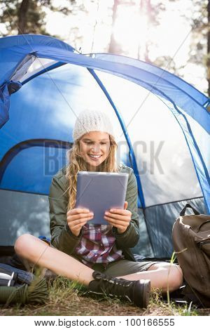 Pretty blonde camper using tablet and sitting in tent in the nature