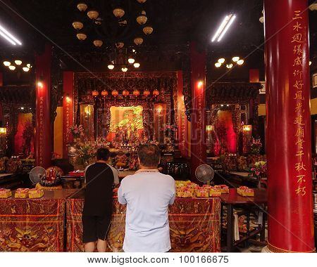 Two Men Pray At The Altar Of A Temple In Taiwan