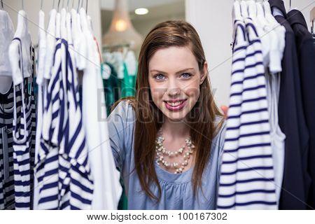 Brunette smiling through clothes rail in fashion boutique