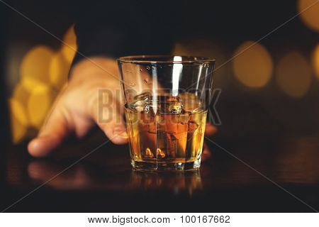 Whiskey glass tumbler in male hand on bar counter