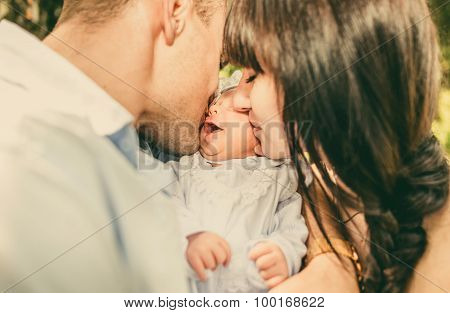 Mother And Father And Her Newborn Baby Outdoor In The Park