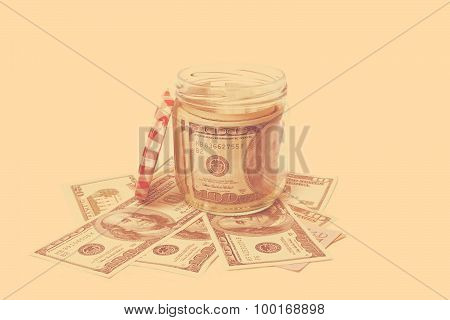 Dollar banknotes in a glass jar