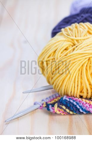 needles and skeins of yellow yarn on a wooden table