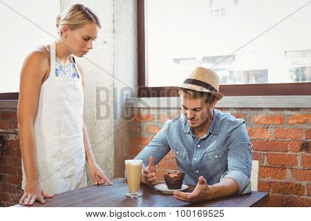Handsome hipster complaining to blonde waitress at coffee shop